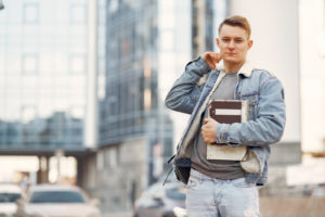 Canva - Man in Blue Denim Jacket Holding Books (1)