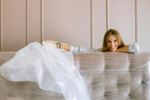 Canva - Woman Smiling Behind the Headboard